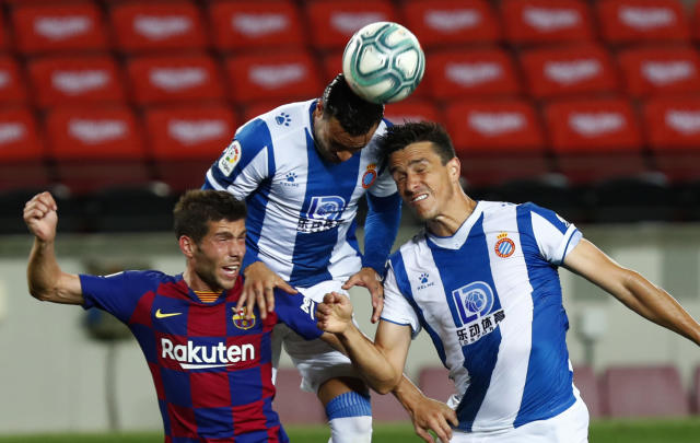 Barcelona's Sergi Roberto fights for the ball against Espanyol's Raul De Tomas and Bernardo Espinosa, right, during the Spanish La Liga soccer match between FC Barcelona and RCD Espanyol at the Camp Nou stadium in Barcelona, Spain, Wednesday, July 8, 2020. (AP Photo/Joan Monfort)