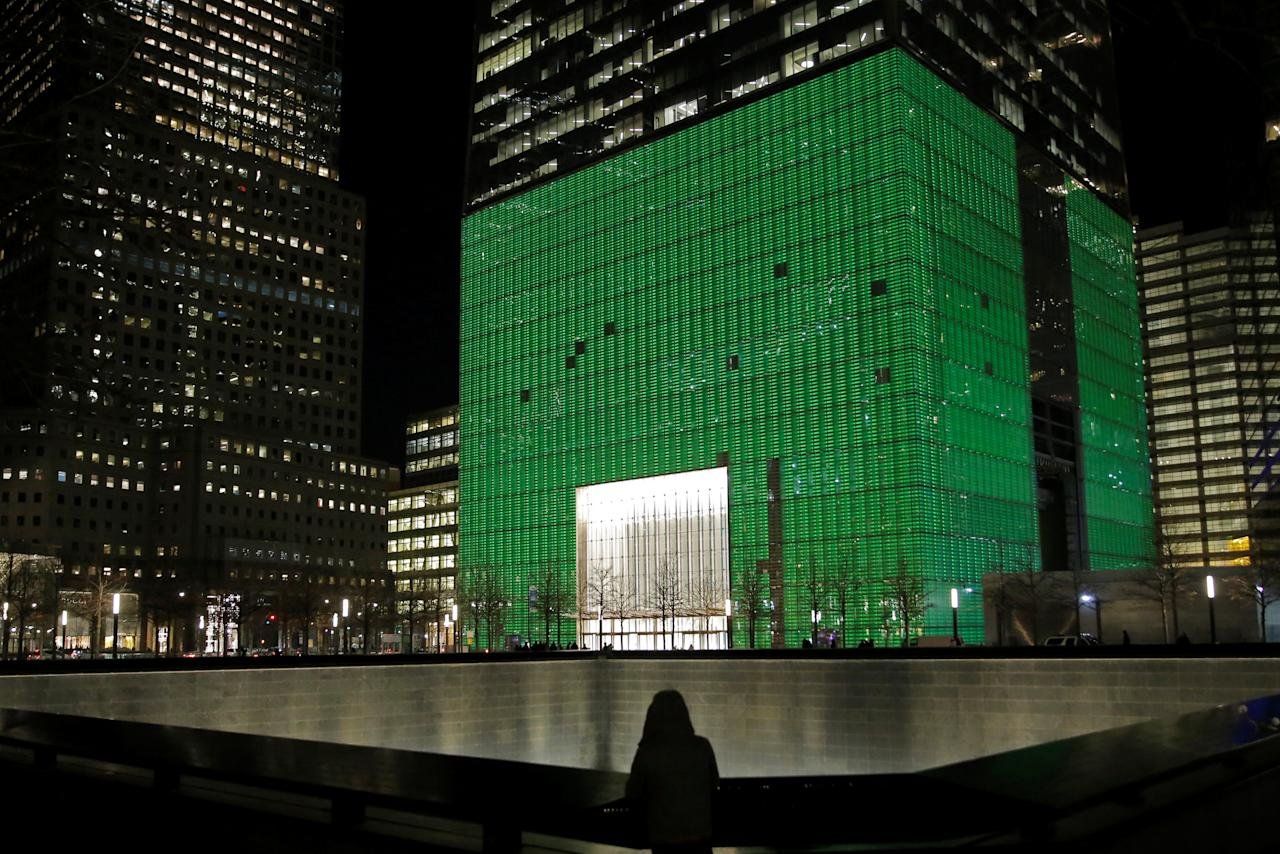 A visitor to the National September 11 Memorial and Museum stands in front of One World Trade Center, which was lit green for St. Patrick's day, in Manhattan, New York, U.S., March 17, 2017.  REUTERS/Andrew Kelly