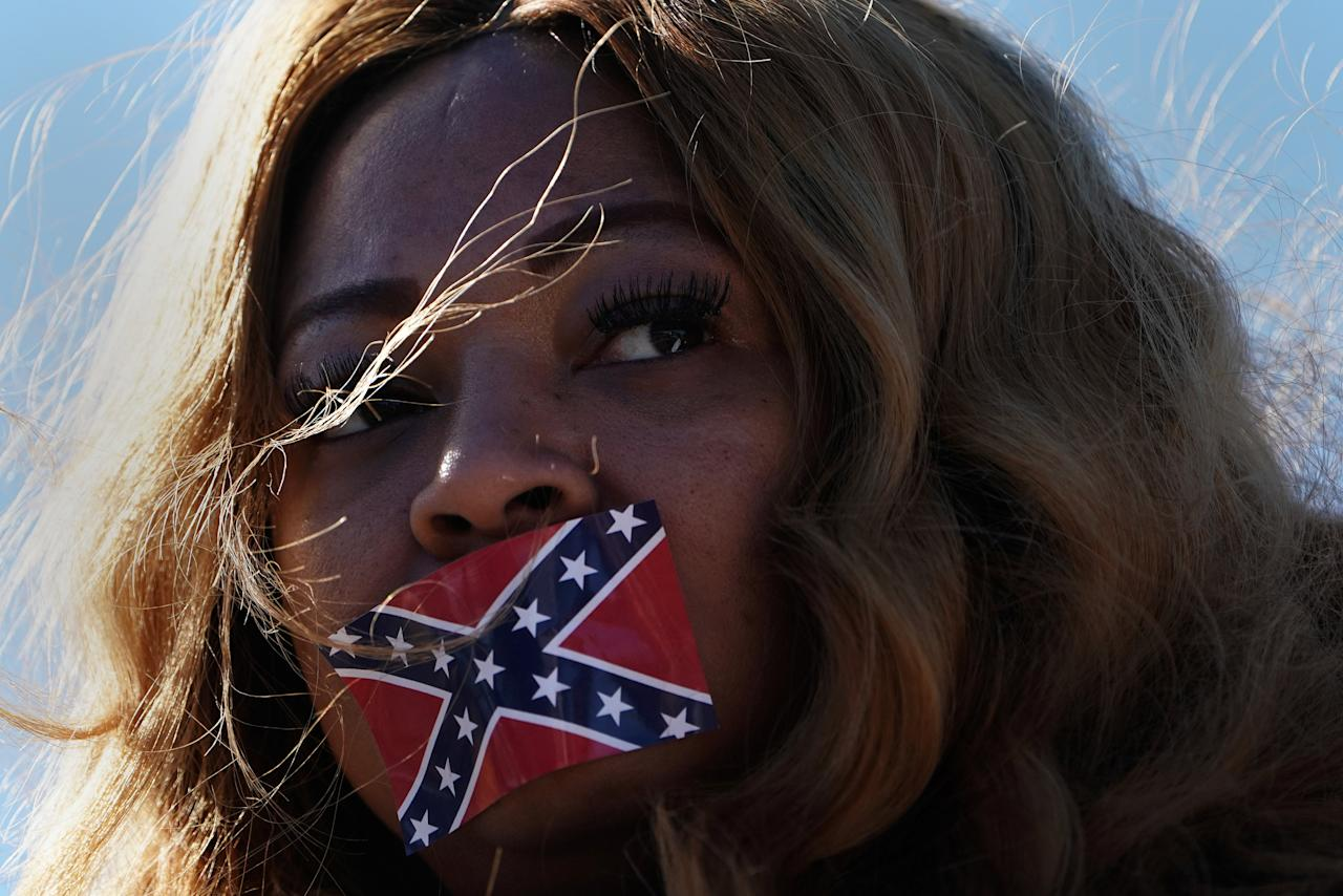 <p>Edelia Carthan stands in silent protest with a confederate flag sticker covering her mouth during the official opening ceremony for the Mississippi Civil Rights Museum in Jackson, Miss., Dec. 9, 2017. (Photo: Carlo Allegri/Reuters) </p>