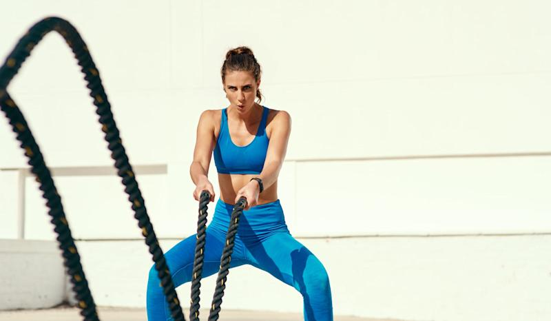 Shot of a sporty young woman working out with battle ropes