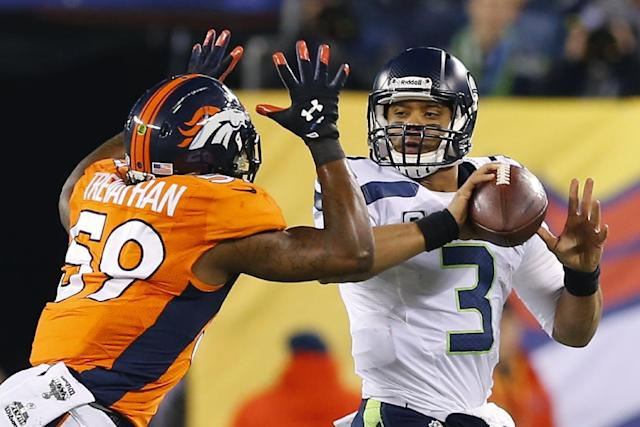 Seattle Seahawks' Russell Wilson (3) looks to pass under pressure from Denver Broncos Danny Trevathan (59) during the first half of the NFL Super Bowl XLVIII football game Sunday, Feb. 2, 2014, in East Rutherford, N.J. (AP Photo/Paul Sancya)