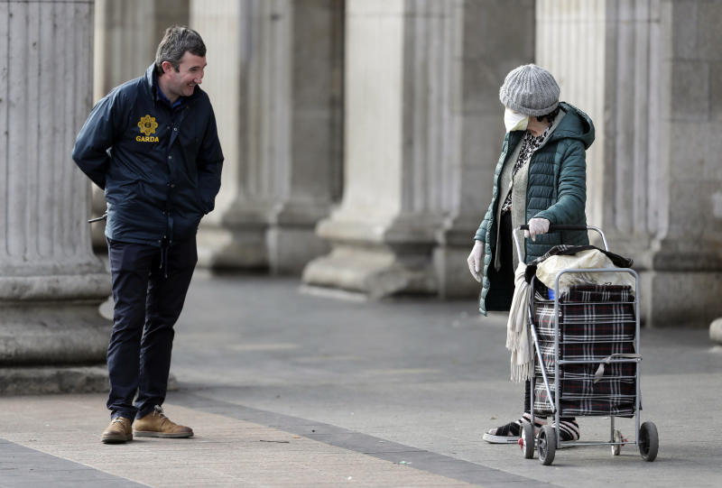A police officer talks to a person at a checkpoint in Dublin, Ireland, Friday April 3, 2020, as restrictions are put in place to prevent the spread of the coronavirus. The new coronavirus causes mild or moderate symptoms for most people, but for some, especially older adults and people with existing health problems, it can cause more severe illness or death. (Niall Carson/PA via AP)