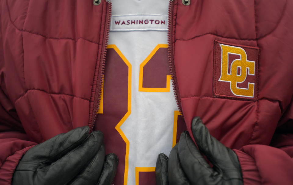 """Washington NFL jersey shows just """"Washington"""" with a red jacket worn over the top with the logo replaced with a gold """"DC"""" emblem."""