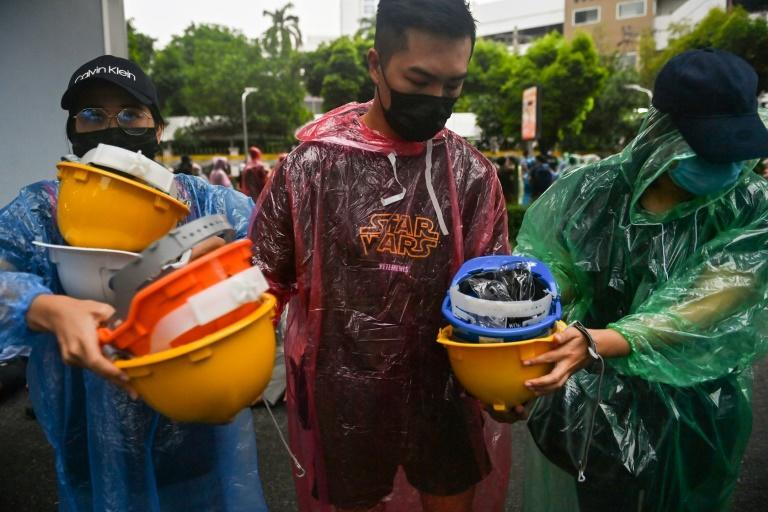 Protesters hand out hard hats during an anti-government rally at Victory Monument in Bangkok