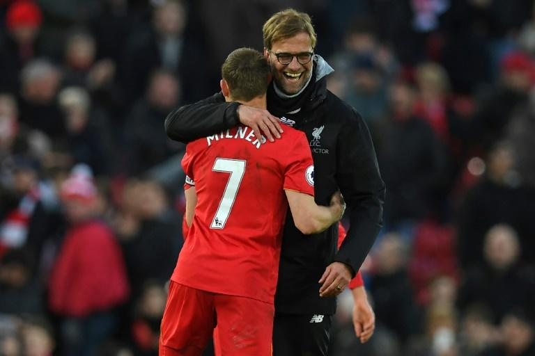 Liverpool's manager Jurgen Klopp (R) embraces midfielder James Milner after their English Premier League match against Burnley, at Anfield in Liverpool, on March 12, 2017