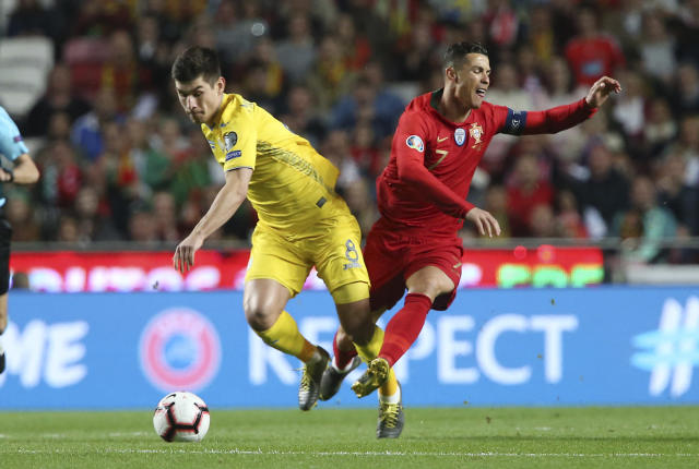 Portugal's Cristiano Ronaldo, right, challenges for the ball with Ukraine's Ruslan Malinovskyi during the Euro 2020 group B qualifying soccer match between Portugal and Ukraine at the Luz stadium in Lisbon, Friday, March 22, 2019. (AP Photo/Armando Franca)