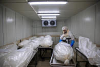 "A worker from ""Hevra Kadisha,"" Israel's official Jewish burial society, prepares bodies before a funeral procession at a special morgue for COVID-19 victims, during a nationwide lockdown to curb the spread of the coronavirus, in the central Israeli city of Holon, near Tel Aviv, Monday, Oct. 12, 2020. (AP Photo/Oded Balilty)"