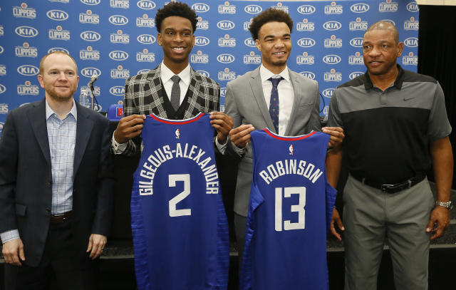 "Lawrence Frank and Doc Rivers introduced <a class=""link rapid-noclick-resp"" href=""/ncaab/players/141954/"" data-ylk=""slk:Shai Gilgeous-Alexander"">Shai Gilgeous-Alexander</a> and <a class=""link rapid-noclick-resp"" href=""/ncaab/players/131633/"" data-ylk=""slk:Jerome Robinson"">Jerome Robinson</a> at the <a class=""link rapid-noclick-resp"" href=""/nba/teams/lac"" data-ylk=""slk:Clippers"">Clippers</a>' training facility Monday. (AP Photo)"