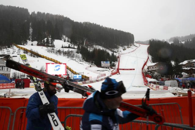 Skiers carry their skiis after an alpine ski, men's World Cup downhill was canceled due to bad weather, in Val Gardena, Italy, Saturday, Dec. 21, 2019. (AP Photo/Gabriele Facciotti)
