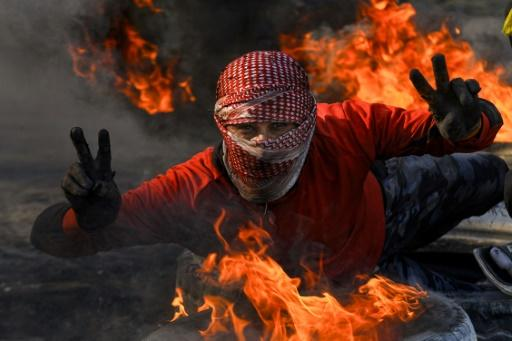An Iraqi protester flashes the victory sign in the holy city of Najaf where demonstrators blocked roads with burning tyres to protest against the nomination of Mohammad Allawi as the country's new prime minister