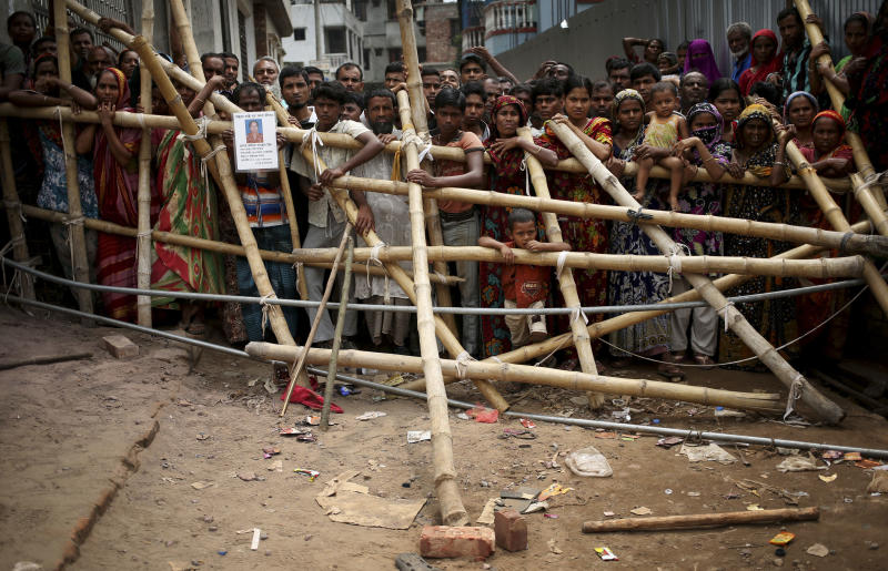Curious onlookers and relatives of missing victims watch from behind a make shift fence as workers start dislodging parts of the garment factory building which collapsed in Savar, near Dhaka, Bangladesh on Monday April 29, 2013. Rescue workers in Bangladesh gave up hopes of finding any more survivors in the remains of a building that collapsed five days ago, and began using heavy machinery on Monday to dislodge the rubble and look for bodies - mostly of workers in garment factories there. At least 381 people were killed when the illegally constructed, 8-story Rana Plaza collapsed in a heap on Wednesday morning along with thousands of workers in the five garment factories in the building.(AP Photo/Wong Maye-E)