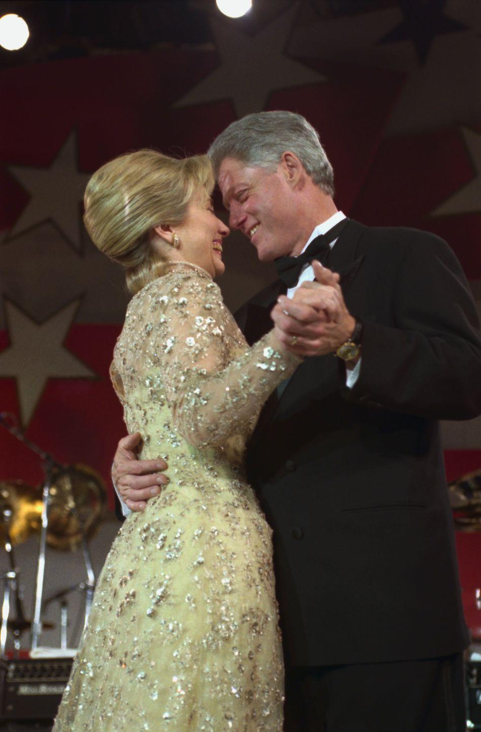 <p>While celebrating his second inauguration, the Clintons shared a dance at the inaugural ball. Hillary Clinton opted for a long-sleeve lace gold gown designed by Oscar de la Renta. </p>