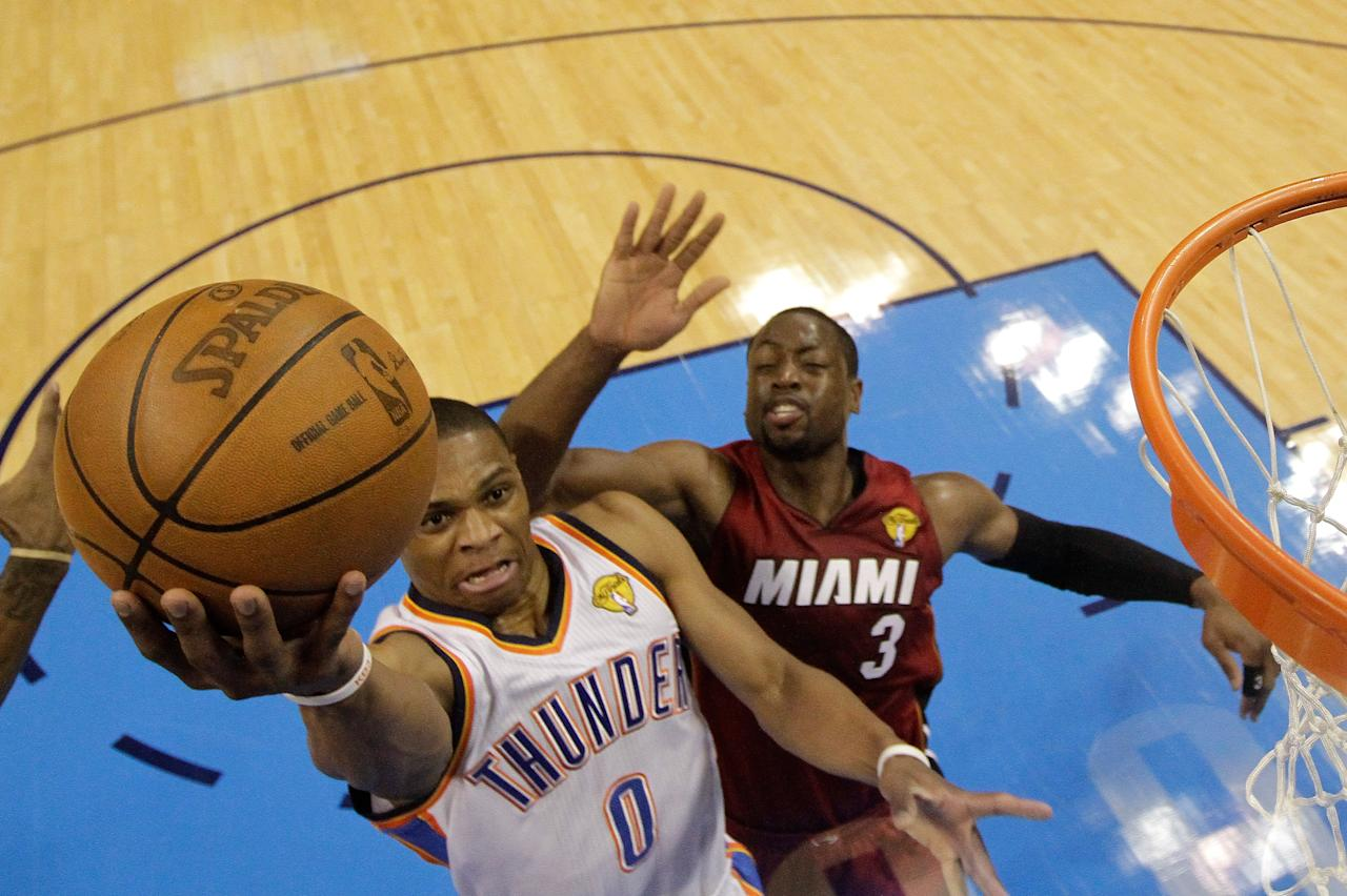 OKLAHOMA CITY, OK - JUNE 12:  Russell Westbrook #0 of the Oklahoma City Thunder goes up for a layup in front of Dwyane Wade #3 of the Miami Heat in the first half in Game One of the 2012 NBA Finals at Chesapeake Energy Arena on June 12, 2012 in Oklahoma City, Oklahoma. NOTE TO USER: User expressly acknowledges and agrees that, by downloading and or using this photograph, User is consenting to the terms and conditions of the Getty Images License Agreement.  (Photo by Jeff Roberson/Pool/Getty Images)