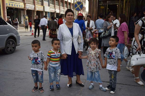 PHOTO: This file photo taken on June 4, 2019, shows a Uighur woman waiting with children on a street in Kashgar in China's northwest Xinjiang region. (Greg Baker/AFP via Getty Images, FILE)