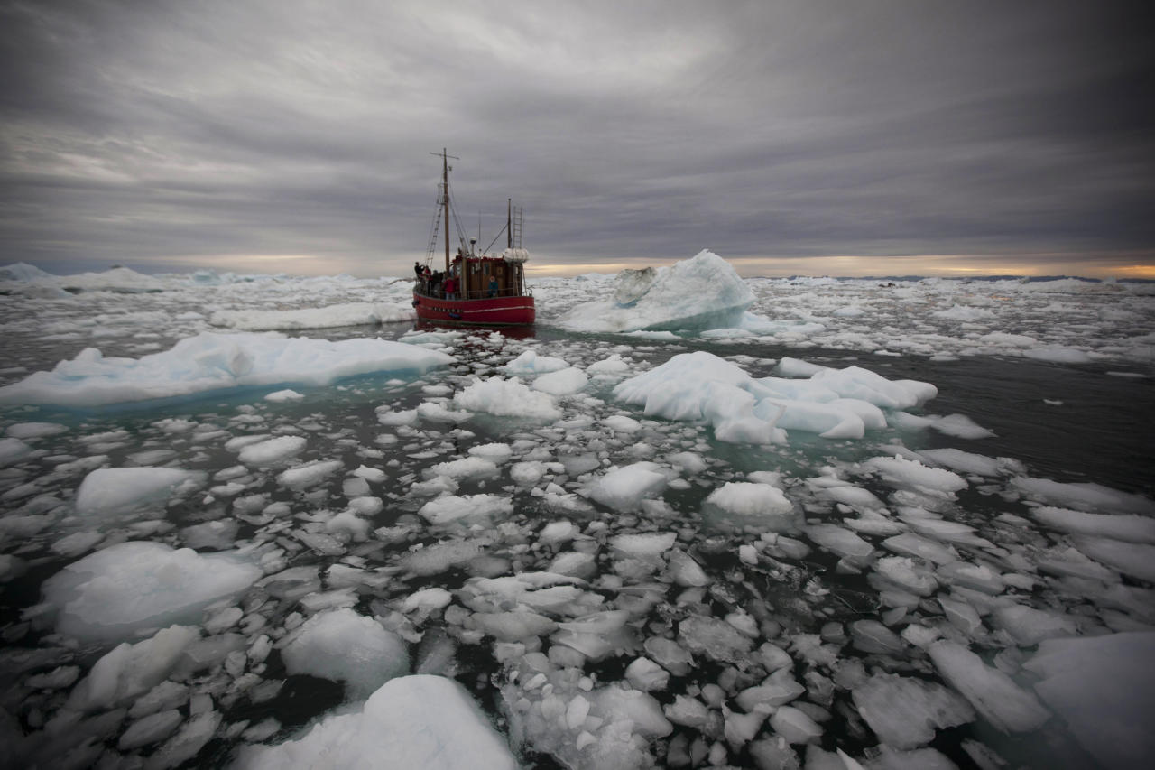 In this July 18, 2011 photo, a boat steers slowly through floating ice, left over from broken-up icebergs shed from the Greenland ice sheet, outside Ilulissat, Greenland. (AP Photo/Brennan Linsley)