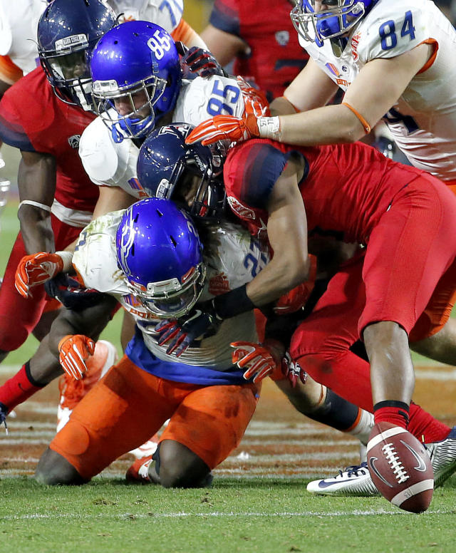 Arizona cornerback Cam Denson, right, forces Boise State running back Jay Ajayi to fumble during the second half of the Fiesta Bowl NCAA college football game, Wednesday, Dec. 31, 2014, in Glendale, Ariz. Arizona recovered the ball. (AP Photo/Ross D. Franklin)