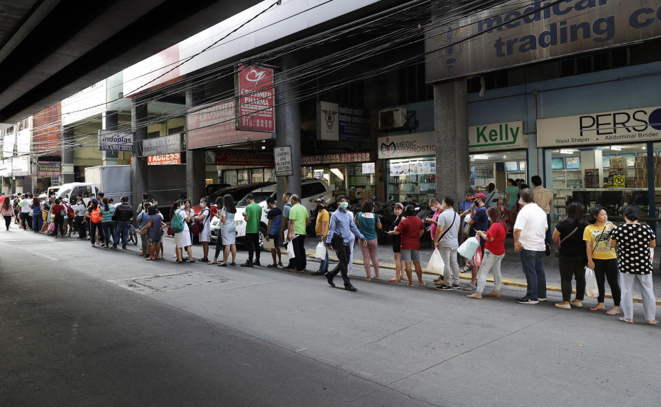 FILE - In this Jan. 30, 2020, file photo, people wait along a road to buy protective face masks at a store in Manila, Philippines. Fear of the spreading coronavirus has led to a global run on sales of face masks despite medical experts' advice that most people who aren't sick don't need to wear them. (AP Photo/Aaron Favila, File)