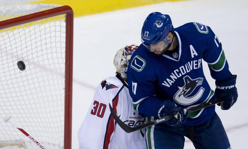 Vancouver Canucks centre Ryan Kesler (17) watches as teammate Vancouver Canucks left wing Daniel Sedin's shot goes past Washington Capitals goalie Michal Neuvirth (30) during the third period of NHL hockey action in Vancouver, British Columbia on Monday, Oct. 28, 2013. (AP Photo/The Canadian Press, Jonathan Hayward)