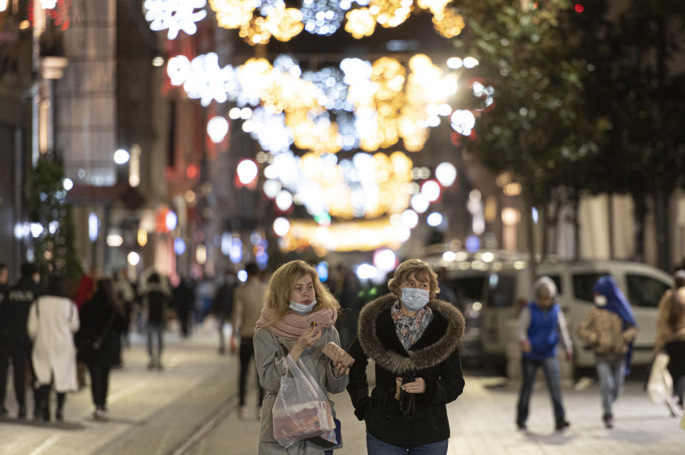 People, wearing masks to help curb the spread of the coronavirus, walk in Istiklal street, the main shopping street in Istanbul, late Wednesday, Nov. 25, 2020. The number of daily COVID-19 infections in Turkey jumped to above 28,000 on Wednesday after, in a surprise development, the government resumed publishing all positive cases and not just the number of patients being treated for symptoms of the coronavirus.The government was accused of hiding the full extent of the virus spread in Turkey, after it was revealed that the number of asymptomatic cases were not being included in data published since July 29. (AP Photo)
