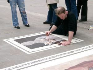 Artist painting on the floor in public