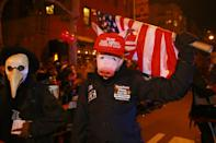 <p>A man wearing a pig mask and an anti-Trump hat carries a U.S. flag in the 44th annual Village Halloween Parade in New York City on Oct. 31, 2017. (Photo: Gordon Donovan/Yahoo News) </p>