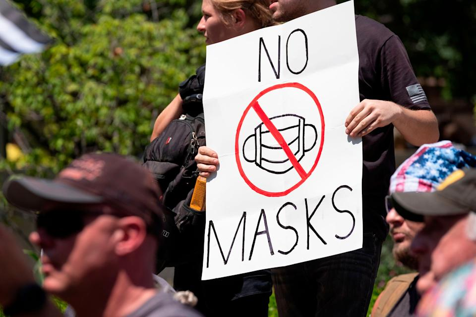 An anti-mask protester holds up a sign in front of the Ohio Statehouse during a protest in July. (Photo: JEFF DEAN via Getty Images)