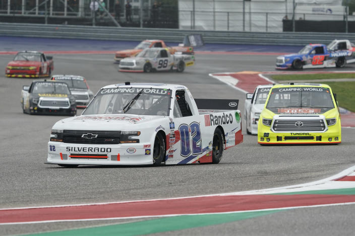Kaz Grala (02) leads the field into Turn 13 on the first lap of the NASCAR Truck Series auto race at the Circuit of the Americas in Austin, Texas, Saturday, May 22, 2021. (AP Photo/Chuck Burton)