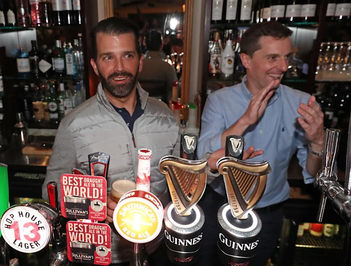 Donald Trump Jr., left, pours drinks and meets locals in the village of Doonbeg in County Clare, Ireland. (Photo Niall Carson/PA Images via Getty Images)