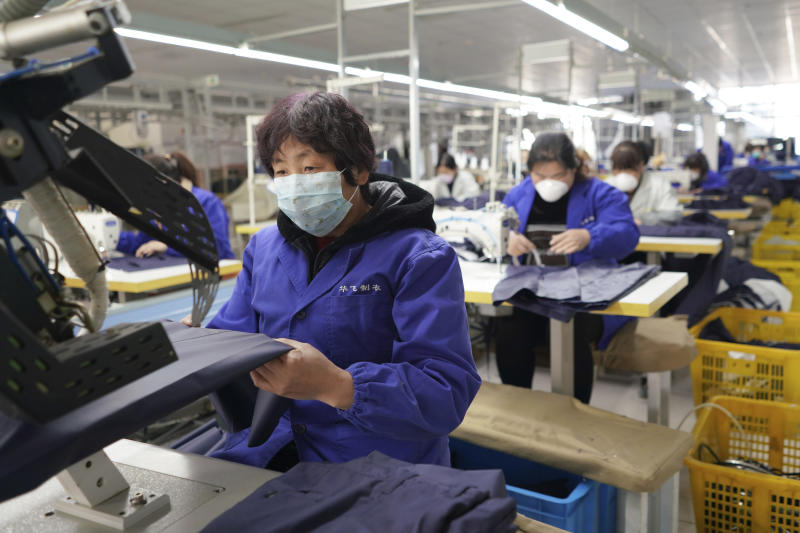 In this March 4, 2020 photo released by Xinhua News Agency, workers labor in a garment workshop while wearing masks at a foreign trade company in Neiqiu County of Xingtai City, north China's Hebei Province. China's exports fell by double digits in January and February as anti-virus controls closed factories, while imports sank by a smaller margin. (Zhu Xudong/Xinhua via AP)