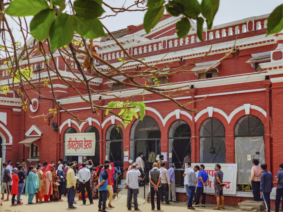 People wait in a queue to test for COVID-19 in Prayagraj, India, Thursday, April 8, 2021. India now has a seven-day rolling average of more than 80,000 cases per day and has reported 12.9 million coronavirus cases since the pandemic began, the highest after the United States and Brazil. (AP Photo/Rajesh Kumar Singh)