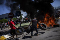 Nissan workers burn tires during a protest in front of the Nissan factory in Barcelona, Spain, Thursday, May 28, 2020. Japanese carmaker Nissan Motor Co. has decided to close its manufacturing plans in the northeastern Catalonia region, resulting in the loss of some 3,000 direct jobs. (AP Photo/Emilio Morenatti)