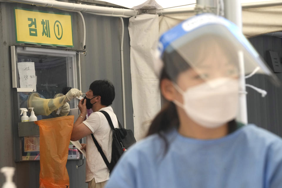A medical worker in a booth takes a nasal sample from a man during coronavirus testing at a makeshift testing site in Seoul, South Korea, Thursday, July 22, 2021. South Korea is reporting 1,842 newly confirmed coronavirus cases for the previous 24 hours - setting a new pandemic single-day record for the second straight day. (AP Photo/Ahn Young-joon)