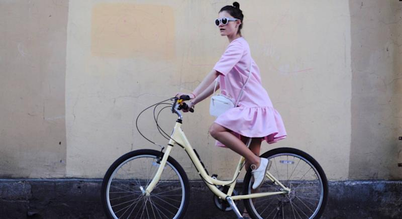 Woman riding her bike in a summer dress [Photo: Getty]