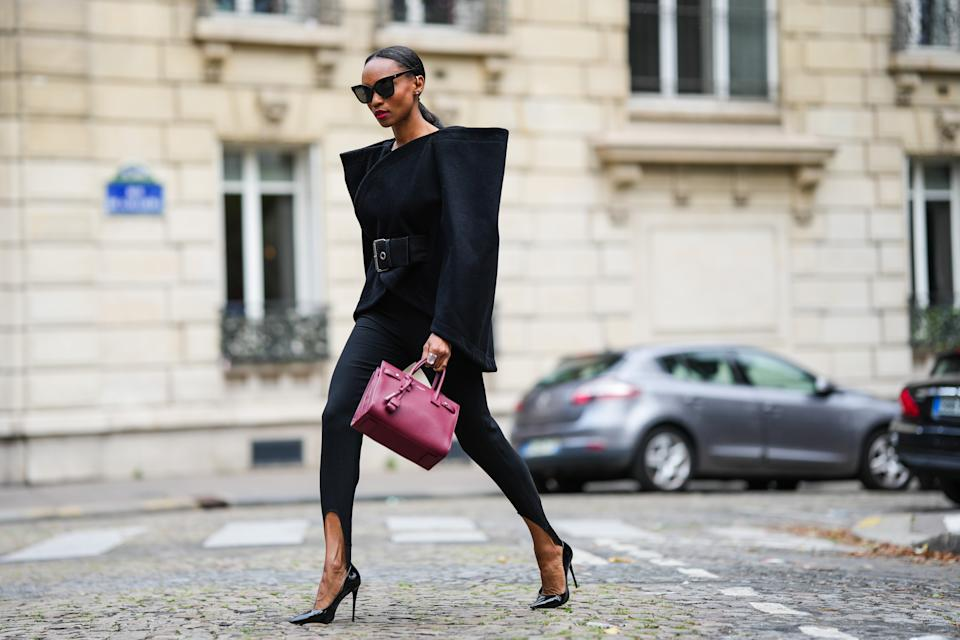 PARIS, FRANCE - SEPTEMBER 18: Emilie Joseph @in_fashionwetrust wears silver earcuffs and earrings by Swarovski Giovanna Engelbert, a large crystal ring, black sunglasses, a black belted wool and cashmere oversized shoulders cape from J.W Anderson, black Stirrup / slit leggings pants, black patent leather pointed pumps heels shoes, a deep red shiny leather Sac De Jour from Saint Laurent Paris / YSL, a black belt, during a street style fashion photo session, on September 18, 2021 in Paris, France. (Photo by Edward Berthelot/Getty Images)