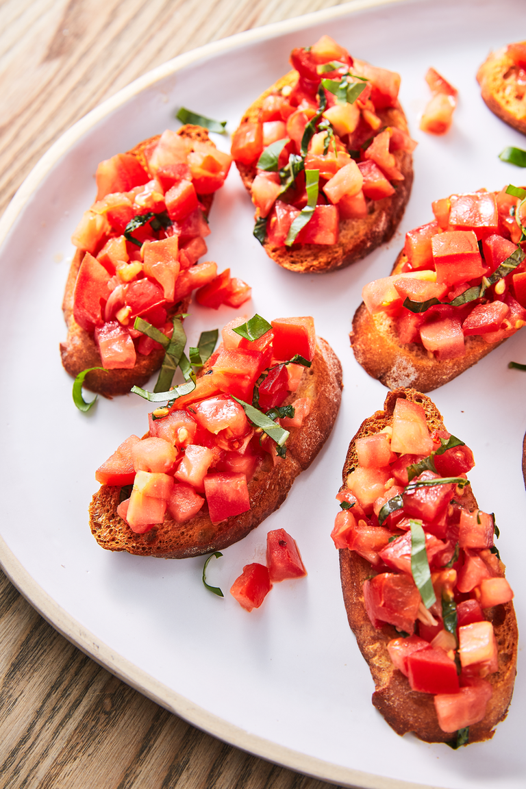 """<p>Nothing screams summer quite like bruschetta. Toasted bread gets rubbed with garlic (don't skip it, it's the best part) and topped with simply marinated tomatoes. The brighter and juicier your tomatoes, the better your bruschetta will be. </p><p>Get the <a href=""""https://www.delish.com/uk/cooking/recipes/a30165416/best-bruschetta-tomato-recipe/"""" rel=""""nofollow noopener"""" target=""""_blank"""" data-ylk=""""slk:Classic Bruschetta"""" class=""""link rapid-noclick-resp"""">Classic Bruschetta</a> recipe.</p>"""