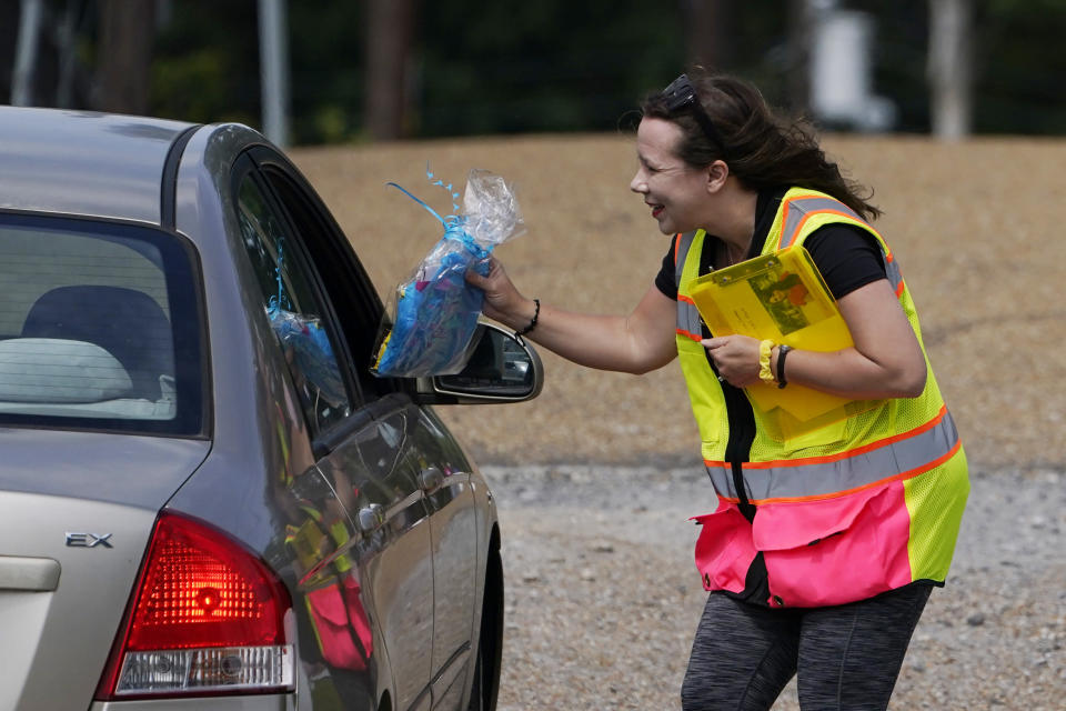 A anti-abortion advocate hands an information packet and candy to the occupants entering the Jackson Womens Health Organization clinic, Thursday, May 20, 2021, in Jackson, Miss. The clinic is Mississippi's only state licensed abortion facility. On May 17, 2021, the U.S. Supreme Court agreed to take up the dispute over a Mississippi ban on abortions after 15 weeks of pregnancy. The issue is the first test of limits on abortion access to go before the conservative majority high court. Their decision could mean more restrictions, and focuses on the landmark 1973 ruling in Roe v. Wade, which established a woman's right to an abortion. (AP Photo/Rogelio V. Solis)
