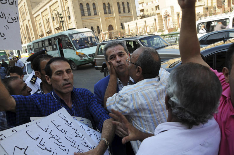 """Supporters of Tawfiq Okasha, center, a popular Egyptian TV presenter accused of inciting the killing of the country's new president on air is kissed by a supporter as he arrives for the opening of his trial, in Cairo, Egypt, Saturday Sept. 1, 2012. Egypt's state news agency said the prosecutor accused Okasha of using his TV program in July and August to incite the killing of President Mohammed Morsi, and of insulting him by calling him an """"illegitimate leader and a liar."""" (AP Photo/Mohammed Assad)"""