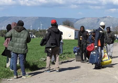 Migrants carry their belongings after a fire broke out at makeshift camp housing hundreds of migrants in the countryside near the village of Rignano Garganico