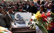 People stand next to the coffin of a supporter of former President Evo Morales killed during clashes with security forces, in Sacaba, Bolivia, Saturday, Nov. 16, 2019. Bolivian security forces clashed with Morales' supporters Friday, leaving at least five people dead, dozens more injured and escalating the challenge to the country's interim government to restore stability. (AP Photo/Juan Karita)