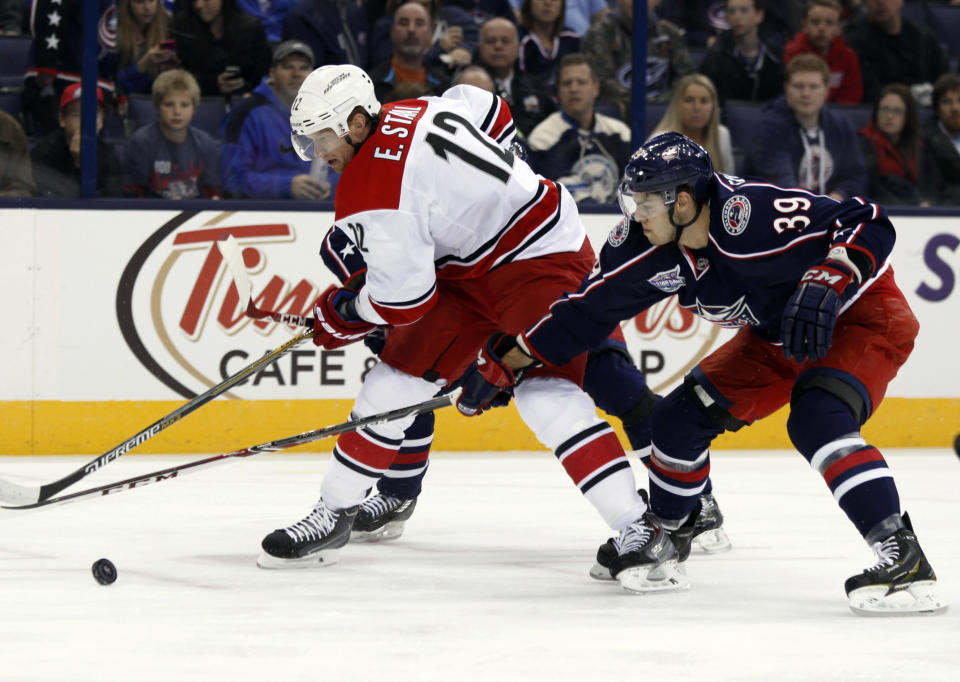 Carolina Hurricanes' Eric Staal, left, works for the puck against Columbus Blue Jackets' Michael Chaput during the first period of an NHL hockey game in Columbus, Ohio, Tuesday, Nov. 4, 2014. (AP Photo/Paul Vernon)