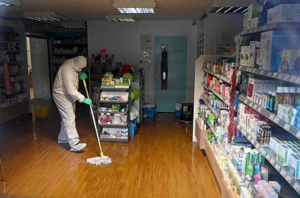 PHOTO: A worker in protective clothing, including face mask and gloves, cleans the floor of the pharmacy attached to the County Oak Medical Centre in Brighton, England, Feb. 10, 2020. (Glyn Kirk/AFP via Getty Images)