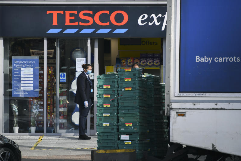 A member of staff from a Tesco express store waits for a delivery in London, Sunday, March 29, 2020. The new coronavirus causes mild or moderate symptoms for most people, but for some, especially older adults and people with existing health problems, it can cause more severe illness or death. (AP Photo/Alberto Pezzali)