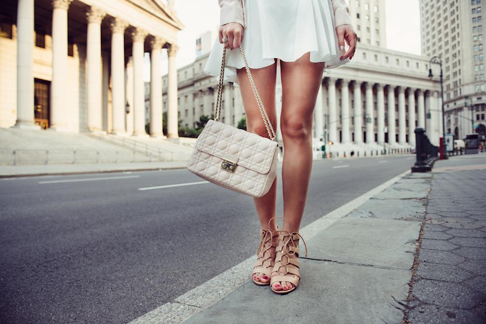 Closeup details of summer female casual street style outfit with luxury bag, skirt and high-heels. Fashionable girl standing at New York City street.