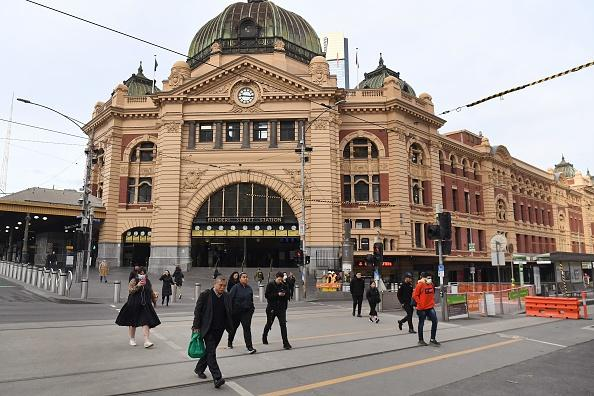 Commuters walk outside the usually bustling Flinders Street station in Melbourne.