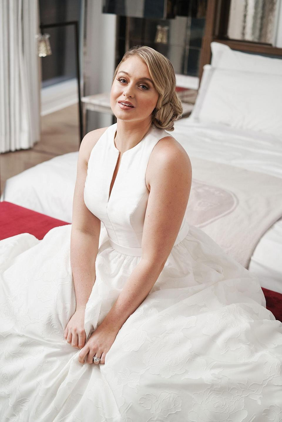 <p>The model wears a simple, classic white a-line dress by Justin Alexander. (Photo: courtesy of Justin Alexander) </p>