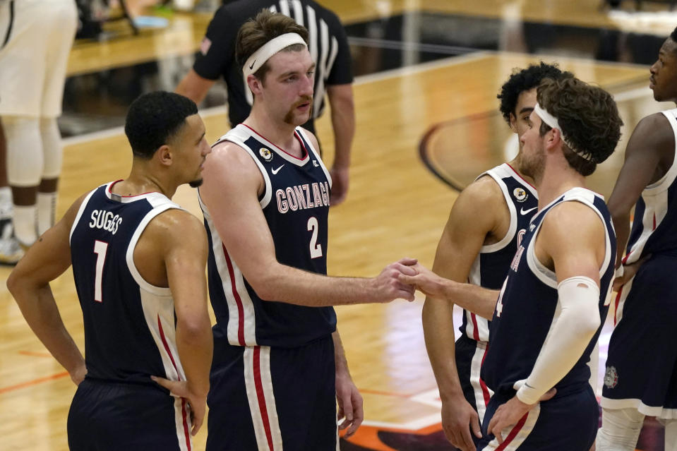 FILE - In this Feb. 4, 2021, file photo, Gonzaga's Drew Timme, second from left, and Corey Kispert shake hands in the closing moments of Gonzaga's 76-58 win over Pacific in an NCAA college basketball game in Stockton, Calif. Gonzaga coach Mark Few isn't being asked questions about where his team should be seeded for next month's NCAA Men's Basketball Tournament. Instead, the longtime coach is getting a different question with a little more than a month until Selection Sunday — does it make any sense for Gonzaga to compete in its conference tournament? (AP Photo/Rich Pedroncelli, File)