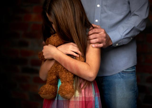 A little girl hugging her teddy bear while a man holds her shoulders.