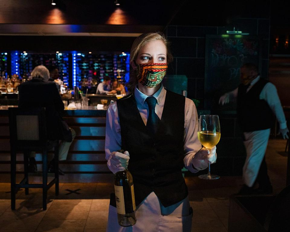 """<div class=""""caption""""> Server Jessica Justice carrying a glass of white wine in the bar area at Ray's On The River. </div> <cite class=""""credit"""">Photo by DUSTIN CHAMBERS</cite>"""