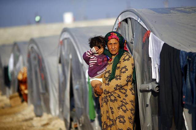 A Kurdish refugee woman from the Syrian town of Kobani carries her child in a camp in the southeastern town of Suruc, Sanliurfa province October 22, 2014. REUTERS/Kai Pfaffenbach (TURKEY - Tags: MILITARY CONFLICT POLITICS)