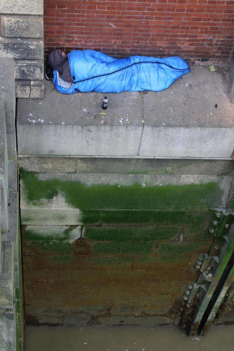 The man was pictured in broad daylight sleeping on a ledge under the bridge near Embankment station (Rex Features)